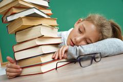 Schoolgirl fell asleep in an embrace with books. Photo of little girl in classroom. Education concept stock photos