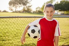 Schoolgirl in football strip holding ball, smiling to camera royalty free stock photos