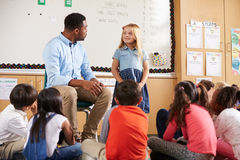 Schoolgirl at front of elementary class with teacher Royalty Free Stock Photography