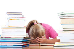Schoolgirl frustated between many books. A school girl lying on desk frustrated between many books stock photo