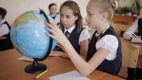 Schoolgirl in geography class studying the countries and continents with the globe. Cute pupils and teacher in classroom with globe at the elementary school stock footage