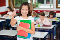 Schoolgirl Gesturing Thumbs Up While Holding Books. Portrait of little schoolgirl gesturing thumbs up while holding books with classmates studying in background Royalty Free Stock Photography