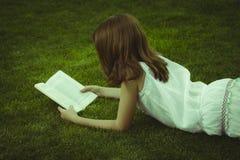 schoolgirl Giovane bella ragazza che legge un libro esterno Immagini Stock Libere da Diritti