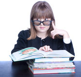 Schoolgirl. Girl in glasses wearing black uniform sits at a table in front of her stack of books. Girl looks left Royalty Free Stock Images