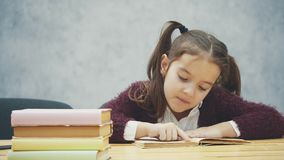 A schoolgirl girl sits on a gray background. During this time the schoolboy reads the book carefully. Diligent student stock video footage