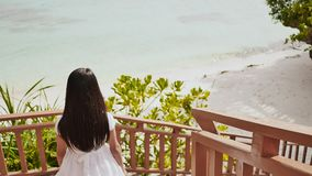 A schoolgirl girl in a summer white dress is walking down a wooden staircase to the tropical coast. Recreation. Summer. Shooting in motion stock video