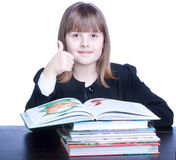 Schoolgirl. Girl wearing black uniform sits at a table in front of her stack of books. Girl shows ok with right hand Royalty Free Stock Photography