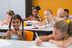 Schoolgirl giving chit to her friends in classroom. At school royalty free stock photo