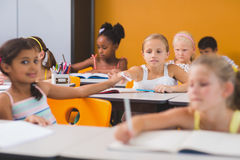 Schoolgirl giving chit to her friends in classroom. At school royalty free stock images