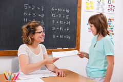 Schoolgirl giving or receiving math test paper royalty free stock image