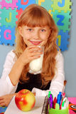 Schoolgirl with glass of milk and an apple Royalty Free Stock Photos