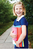 Schoolgirl goes to school with textbooks. Royalty Free Stock Photo