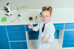 Schoolgirl in goggles holding reagents in flasks in chemical lab Royalty Free Stock Photos