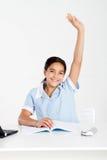 Schoolgirl hand up. In classroom Stock Photo