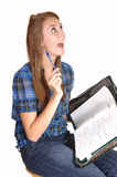 Schoolgirl has an idea. A teenage schoolgirl sitting on a chair with her notebook on her lap, having an idea about her homework, for white background stock photo