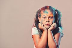 Schoolgirl has paint spots on face. Children and creativity concept stock images