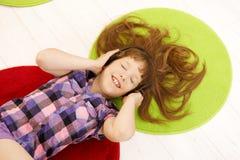 Schoolgirl having fun with headphones Stock Images