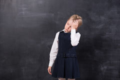 Schoolgirl with headache stands at the blackboard Royalty Free Stock Photo