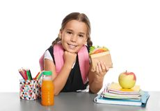 Schoolgirl with healthy food and backpack sitting at table. On white background royalty free stock photos