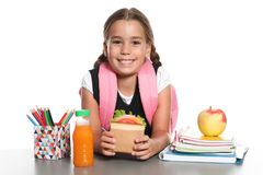 Schoolgirl with healthy food and backpack sitting at table. On white background royalty free stock photography