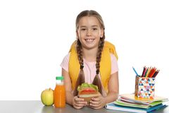 Schoolgirl with healthy food and backpack sitting at table. On white background stock photo