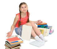 Schoolgirl among a heap of books Royalty Free Stock Images
