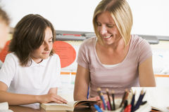 A schoolgirl and her teacher reading in class Stock Image