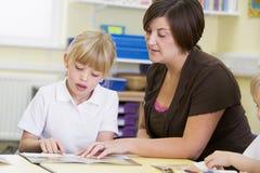 A schoolgirl and her teacher reading in class