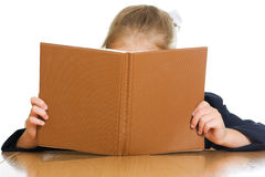 Schoolgirl is hiding behind a book Royalty Free Stock Photography