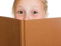 Schoolgirl is hiding behind a book Royalty Free Stock Photo