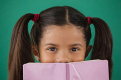 Schoolgirl hiding behind a book against green background Stock Photos