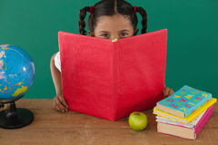 Schoolgirl hiding behind a book against green background Stock Photo