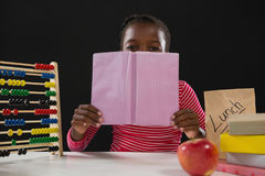 Schoolgirl hiding face behind book against black background Stock Image