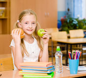 Schoolgirl holding an apple and fast food Royalty Free Stock Photography