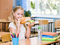 Schoolgirl holding an apple and fast food Stock Image