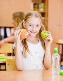 Schoolgirl holding an apple and fast food Royalty Free Stock Photos