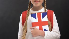 Schoolgirl holding book with British flag, English language studying, lessons. Stock footage stock footage