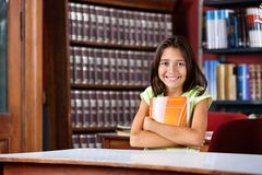 Schoolgirl Holding Book While Sitting At Table In Stock Images
