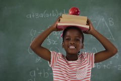 Schoolgirl holding books stack with apple on head against chalkboard Royalty Free Stock Images