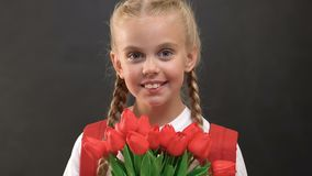 Schoolgirl holding bouquet of tulips and looking at camera, present for teacher. Stock footage stock video footage