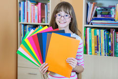 Schoolgirl  holding colored papers Stock Photography