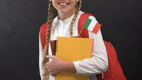 Schoolgirl holding copy books with Italian flag and smiling at camera, language. Stock footage stock video footage