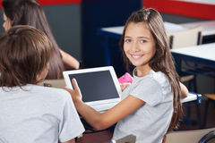 Schoolgirl Holding Digital Tablet At Desk Stock Image