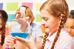 Schoolgirl holding flask with blue reagent at lab royalty free stock photography