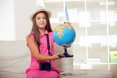Schoolgirl holding globe in hands and exploring Stock Photography