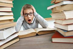 Schoolgirl holding head with opened mouth and crazy facial expression. Photo of girl in classroom around books. Education concept royalty free stock photography