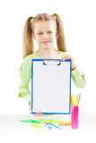 A schoolgirl holding paperclip near table Stock Image