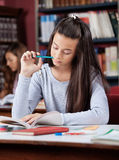Schoolgirl Holding Pen While Reading Book In. Teenage schoolgirl holding pen while reading book at table in library Stock Photos