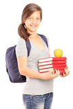 Schoolgirl holding a pile of books and an apple Stock Photo