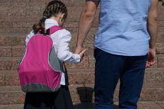 The schoolgirl holds his fathers hand, climbing the steps, on his way to school stock photo